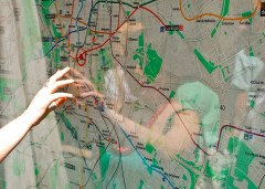 Wall-mounted map with woman pointing to a town