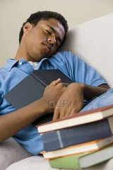 Young man falling asleep holding books