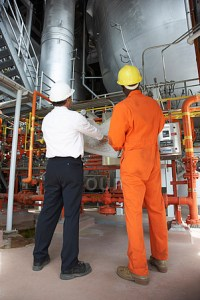 Industrial plant workers checking plans