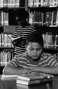 Two young children reading in the library