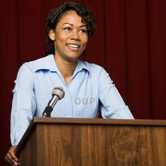Mixed race businesswoman speaking at podium