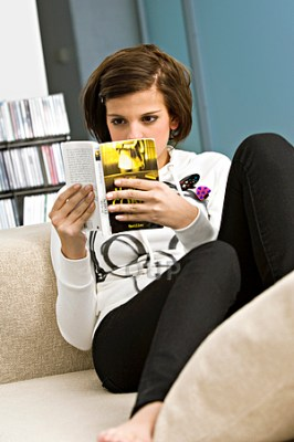 Teenage girl reading on couch