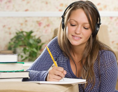 Young woman wearing headphones and writing