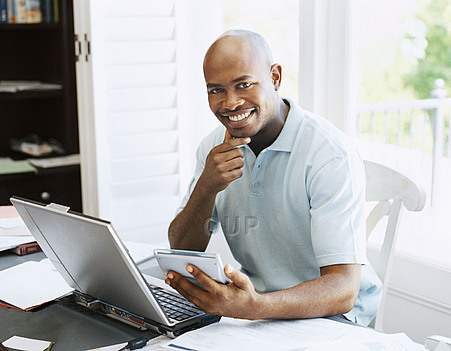 Man sat at desk smiling while working