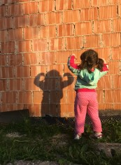 photographs: of a young girl making a pose and looking at her shadow on the wall