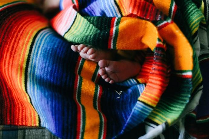 Tiny little newborn feet all cuddled up.