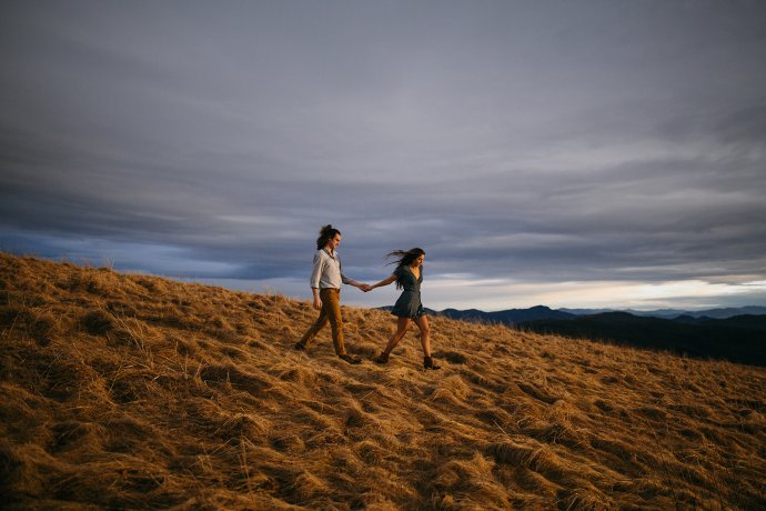Meg & Daniel walking down the side of Max Patch North Carolina at Sunset for their engagement photos