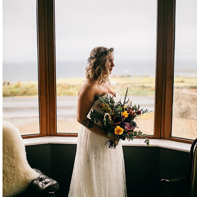 Bride holding bouquet of flowers with a view