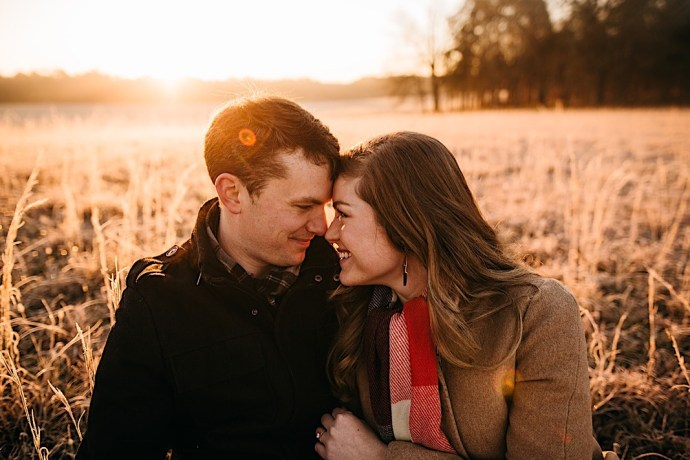 Chattanooga couple posing for their engagement photos in a field