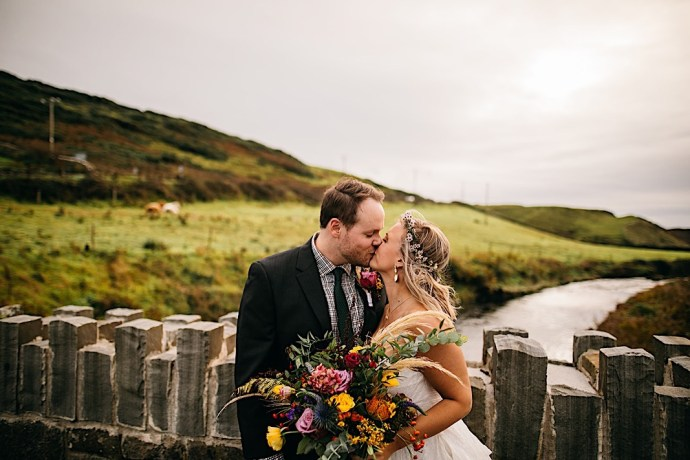 Bride with bouquet and groom kissing in bucolic Ireland