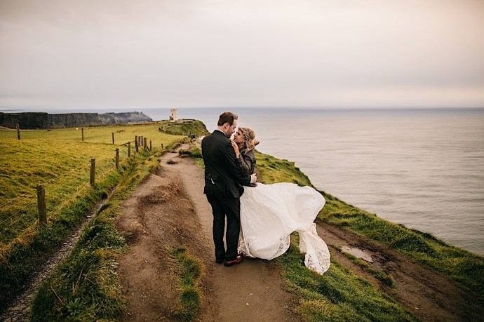 Bride and groom on Cliffs if Moher in Ireland on a windy afternoon