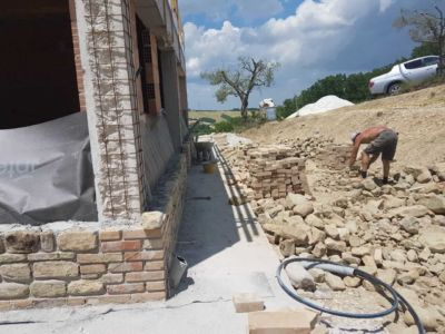 Across the Front of a new stone house in Le Marche