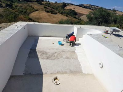 Working to Seal the Pool Concrete on a pool behind a new house in Le Marche
