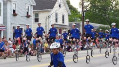 A large group of blue-shirted unicyclists of all ages