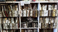 Rows of mortise locks in various finishes and colors line shelves