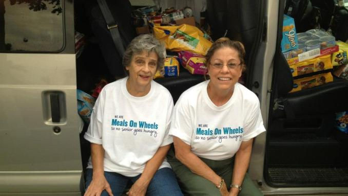 Two volunteers, sitting with collected pet food