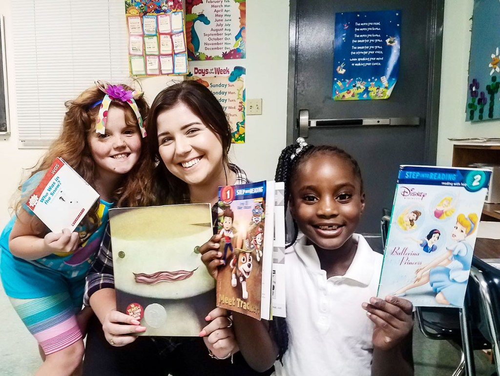 Molly with two readers holding her favorite book, The Stinky Cheese Man by John Scieszka.