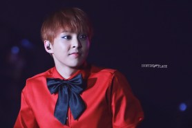 Xiumin in a red shirt with a bow tie