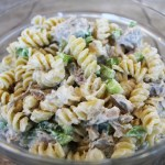 Twisty noodles with green peppers diced, pork, and mirsacle whip mixed together on a clear plate.