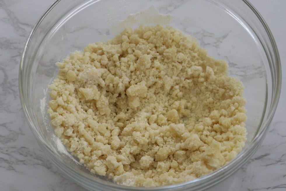 Sugar, cinnamon, flour, and butter mixed together in a glass bowl for a sugary topping
