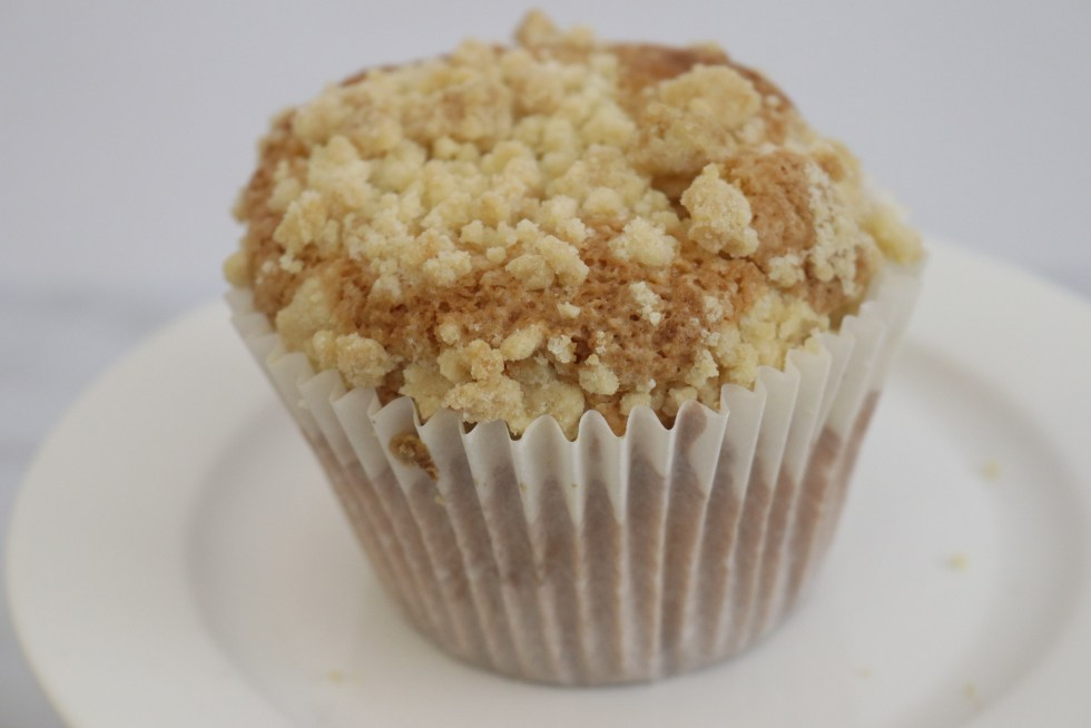 An apple muffin with crumb topping in a white muffin liner on a white plate