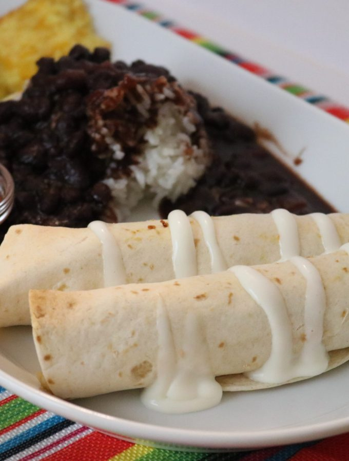 Plate of flautas with crema on them and sides of black beans and rice. salsa. chips, and guacamole