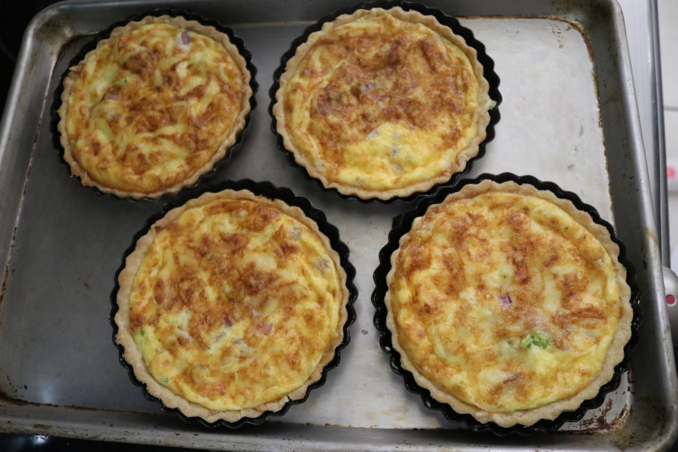 """4 6"""" tart pans filled with quiche"""