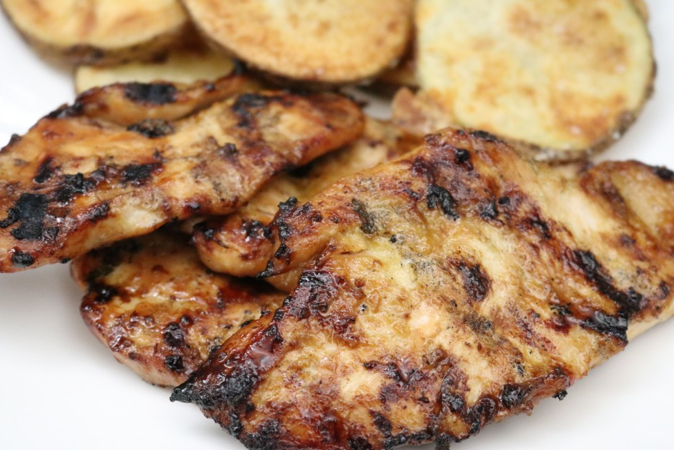 Grilled chicken on a white plate with sliced potatoes