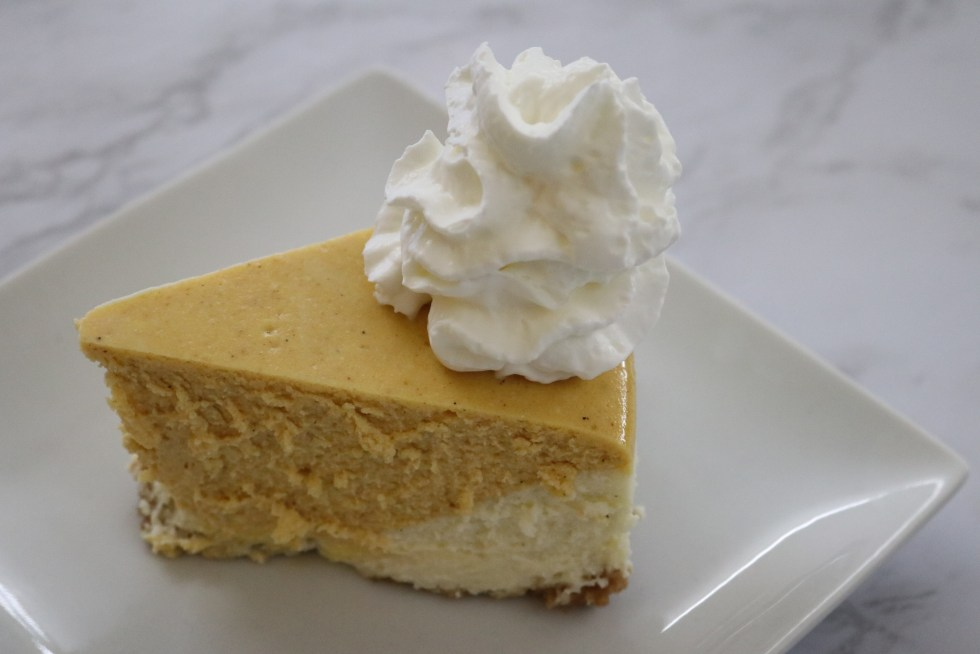 Pumpkin vanilla cheesecake just out of the pan iece of pumpkin vanilla cheesecake on a white plate