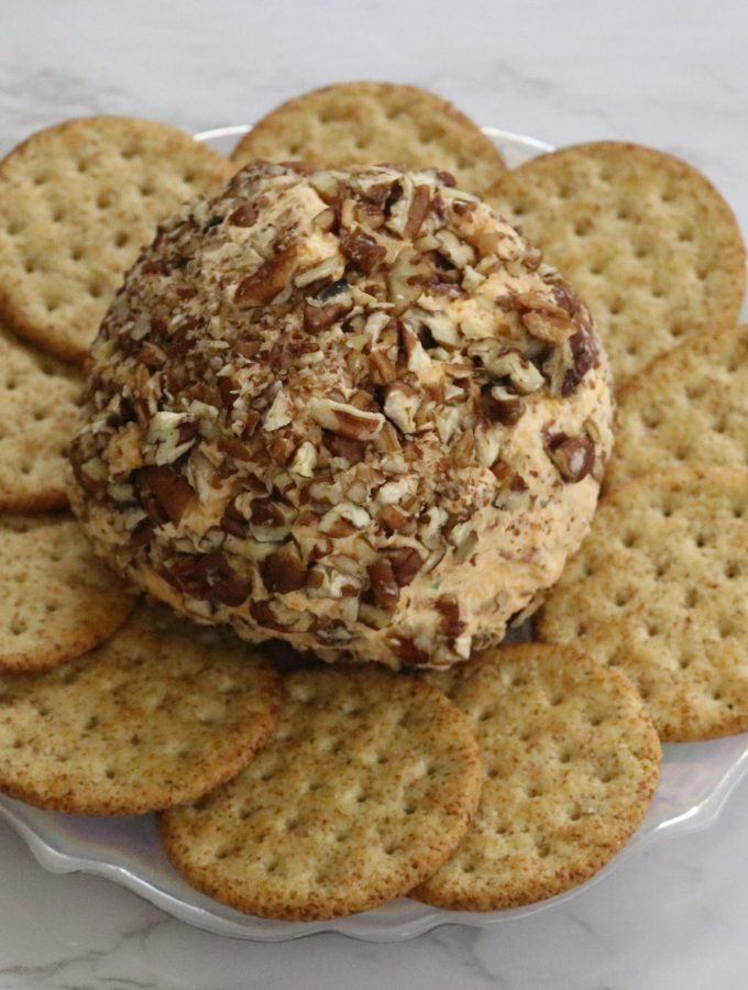 cheese ball with pecans on a plate surrounded by butter crackers