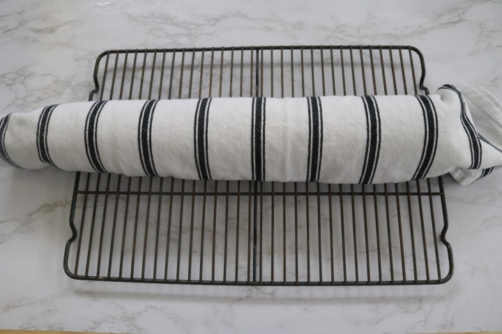 Cake rolled in a tea towel cooling on a rack