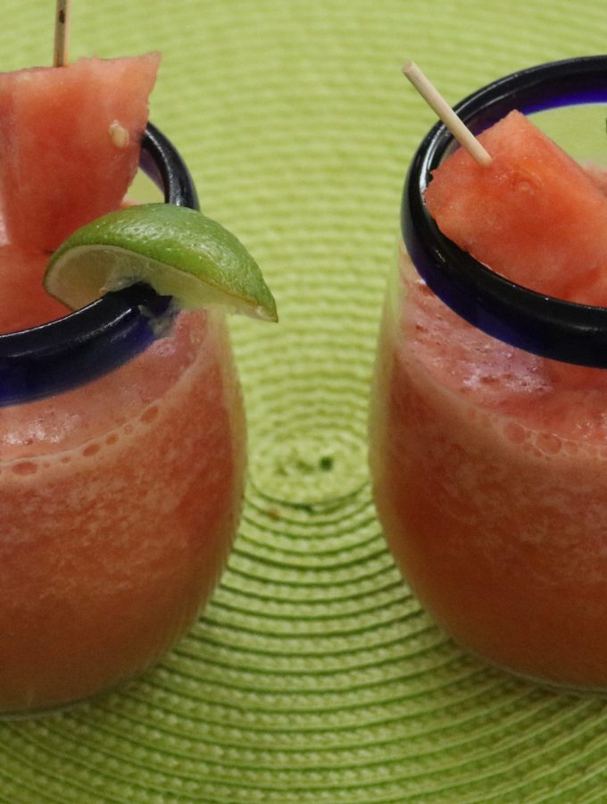 2 glasses of a watermelon mock-tail with a lime wedge and watermelon chunks
