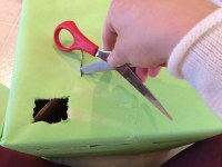 Wrap the leprechaun trap in green paper, and then go back over it with a pair of scissors to cut out the windows.