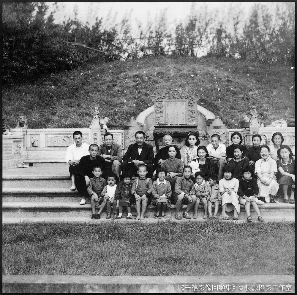 一群黃家人坐在祖先墳墓前合照