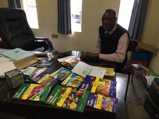 Headmaster Gift Bere looks through the books we'd brought him and the list to order more so that the school could function perfectly.