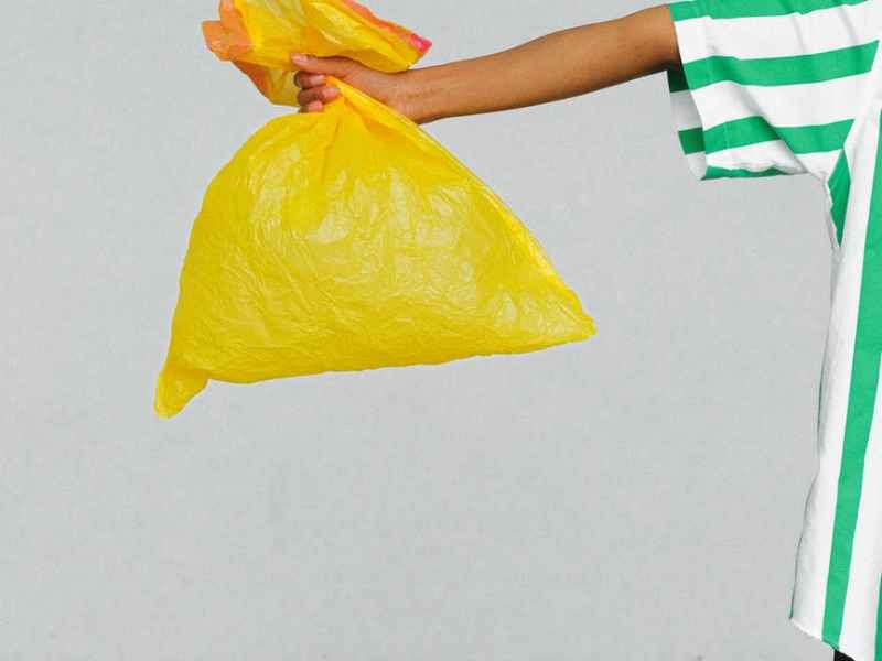 woman in white and green shirt holding yellow plastic bag