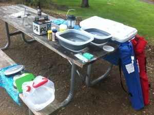 dish washing tubs, a water jug, a lantern and beach chairs are part of our car camping setup