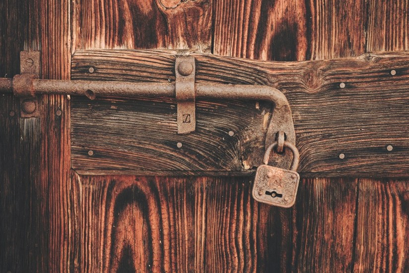 Rusty padlock on wooden door