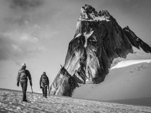 grayscale photo of two people walking on moutain valley