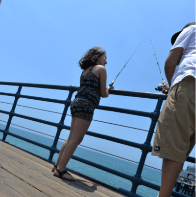 dad fishing with daughter on pier