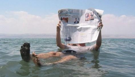 Reading newspaper in the Dead Sea