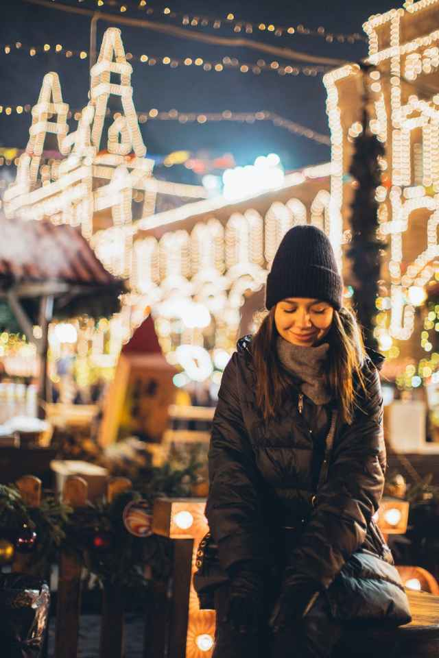 joyful modest woman on square in downtown at new year night