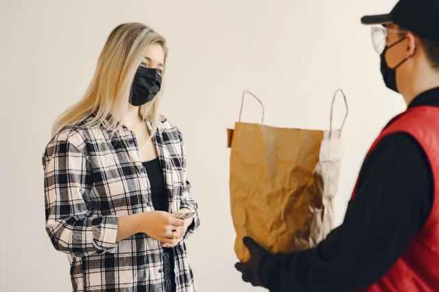 young female customer receiving grocery order during coronavirus pandemic