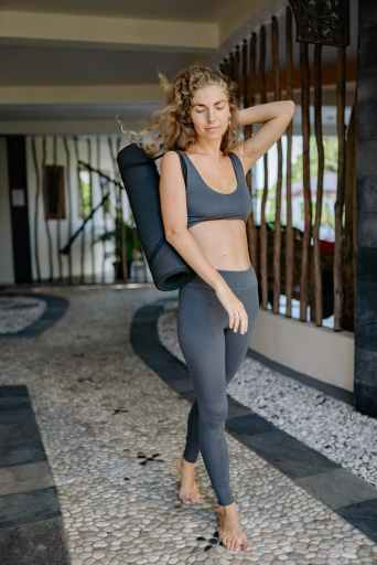 sporty woman in sportswear with yoga mat on pathway move your body