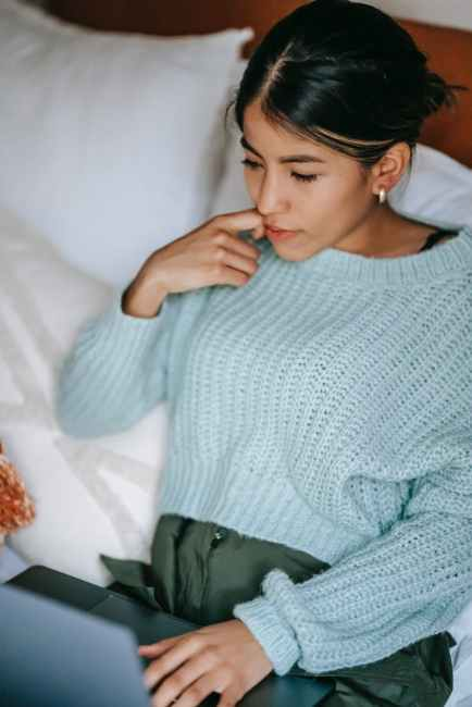 pensive ethnic woman using laptop on bed motivation