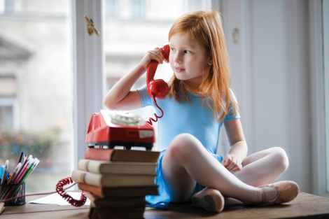 pensive little girl talking on vintage phone while sitting on table in light living room