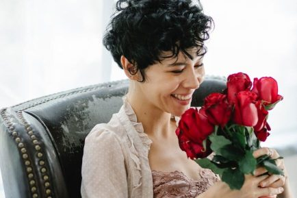 smiling woman with bouquet of roses imposter syndrome