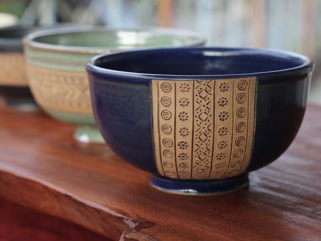 深藍色陶瓷碗放在木頭上,上頭有原住民圖騰紋路的雕刻