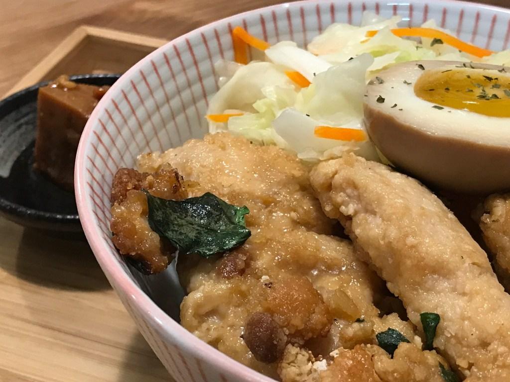 一個陶瓷碗放在木盤上,裡頭裝著豆乳雞,旁邊有溏心蛋、高麗菜,還有一塊豆腐乳