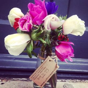 little vase of flowers with handwritten tag